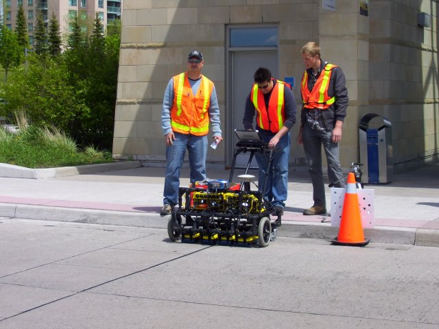Informative Image of multiVIEW technicians operating ground penetrating radar equipment to perform road inspection to determine the location of buried utilities underneath proposed road construction.