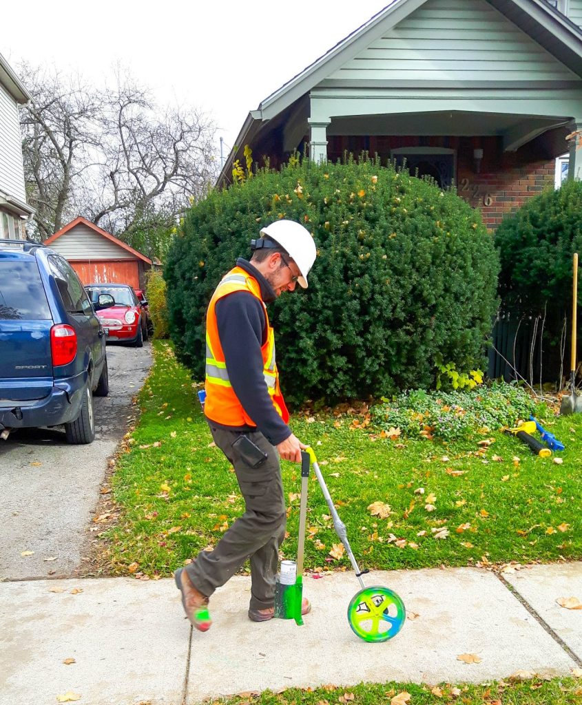 Informative Image of a multiVIEW Utility Locating Technician walking along a sidewalk on a residential street taking horizontal measurements of buried sewer line while marking the sidewalk pavement with green paint stick.