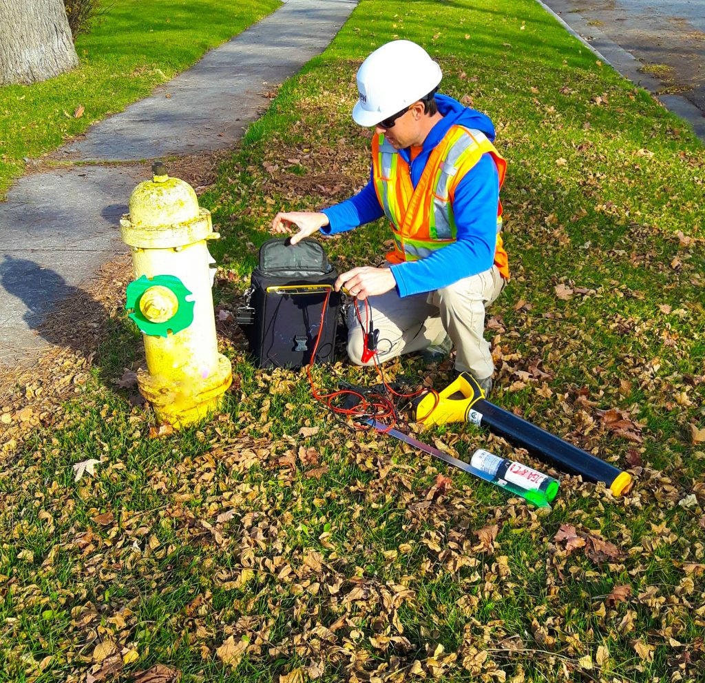 Informative Image of a multiVIEW Utility Locating Technician seen kneeling next to a fire hydrant in the middle of the grass between a residential road and sidewalk. The technician is setting up his Electromagnetic (EM) Induction equipment to accurately identify and ultimately mark he direction of underground water main with his green paint dispensing stick laying on the grass next to him.