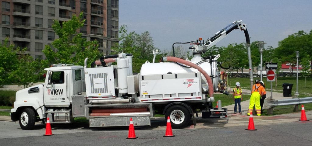 Informative Image shows a multiVIEW Pneumatic Vacuum Excavation truck parked by the curbside of a major roadway near an intersection. Traffic pylons have been placed around the truck to ensure the safety of multiVIEW's technicians. The three on-site technicians are using the suction excavator hose to remove subsurface materials on the right of way of the intersection.