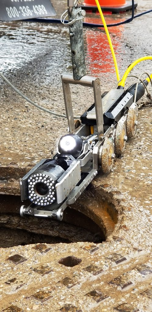 Informative Image displays a close-up view of track mounted CCTV camera sitting next to manhole and being readied to lowered into the sewer line.