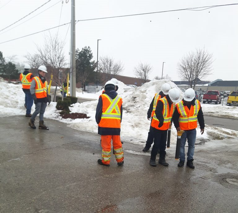 Informative Image of multiVIEW servicing Waterloo region. This photo features Cambridge new technicians receiving field training in a parking lot and road way intersection.